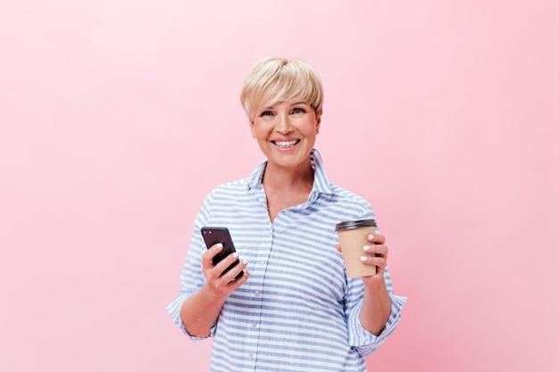 Senhora de bom humor posa com xícara de café e telefone em fundo rosa