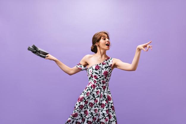 Senhora de bom humor segura bolsa cinza em fundo isolado. linda mulher atraente em um vestido floral com pequena bolsa posando.