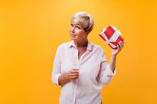 Senhora de cabelo curto balançando a caixa de presente em fundo laranja