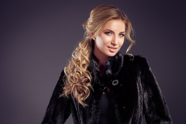 Senhora de cabelo loiro sedutor de moda em um elegante casaco de pele e roupa interior preta