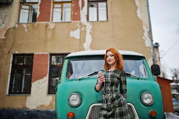 Senhora de cabelo vermelho jovem com celular celular e fones de ouvido, usando vestido verificado no velho ônibus minivan vintage.