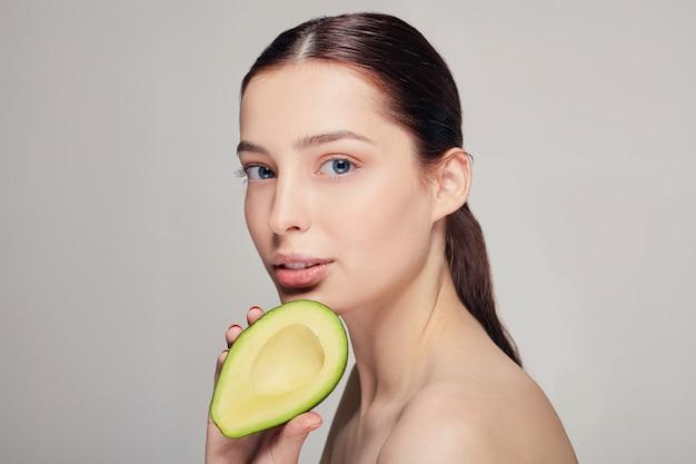 Senhora de cabelos castanho com abacate na mão