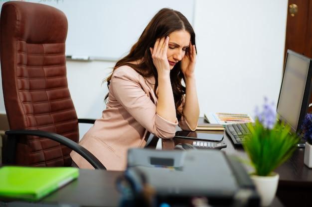 Senhora de cabelos castanhos negócios com cabelos longos, sentado na mesa na cadeira do escritório, olhando para baixo