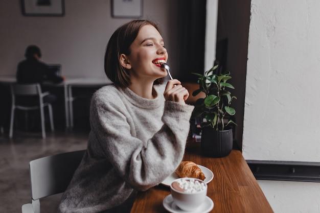 Senhora de cabelos curtos e suéter cinza morde uma colher de chá. retrato de menina com lábios vermelhos, sentado no café e desfrutando de croissant e cappuccino.