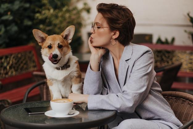 Senhora de cabelos curtos gosta de café no café e olha para o cachorro. mulher encantadora com jaqueta cinza descansando com corgi do lado de fora