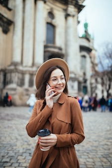 Senhora de cabelos curtos no chapéu falando sobre phote e mensagens de texto em seu telefone