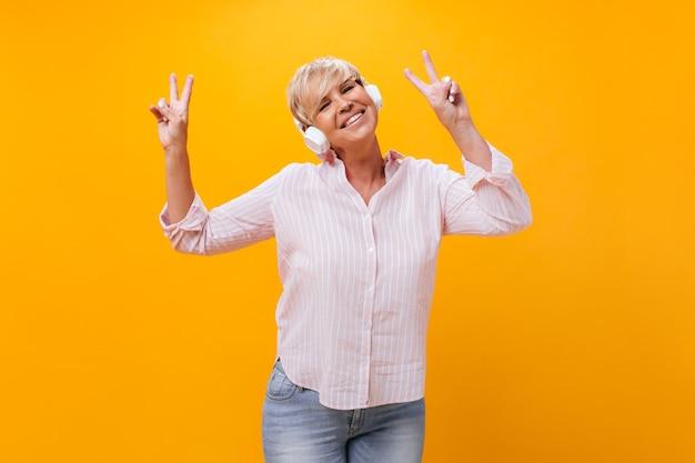 Senhora de cabelos curtos usando fones de ouvido mostra os sinais da paz em fundo laranja