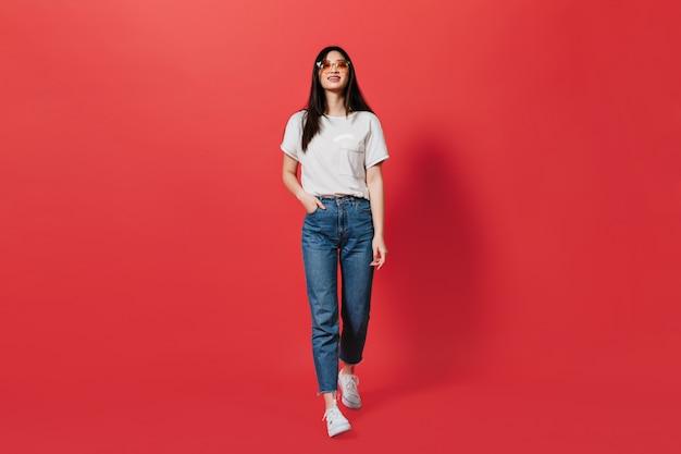 Senhora de cabelos escuros com óculos laranja, vestida de jeans e top move na parede vermelha