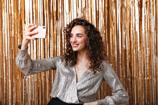 Senhora de cabelos escuros e blusa prateada tirando selfie sobre fundo dourado