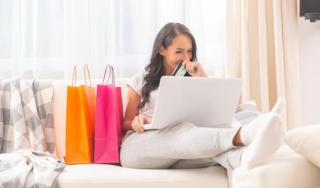 Senhora de cabelos escuros vestida com calças de moletom confortáveis de cor clara e camiseta sorrindo misteriosamente para um laptop segurando um cartão de débito na mão, cobrindo a boca e com duas sacolas de compras ao lado dela.