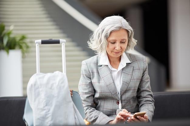 Senhora de cabelos grisalhos, verificando o mensageiro no aeroporto