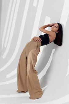 Senhora de calça bege cabelo grosso cosméticos modelo quarto sombra caindo. foto de alta qualidade