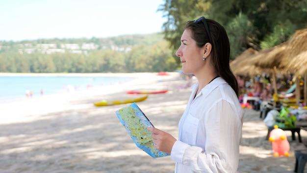 Senhora de camisa branca em pé na praia e olhando para o mapa segue indicações contra pessoas desfocadas descansando e o incrível oceano azul