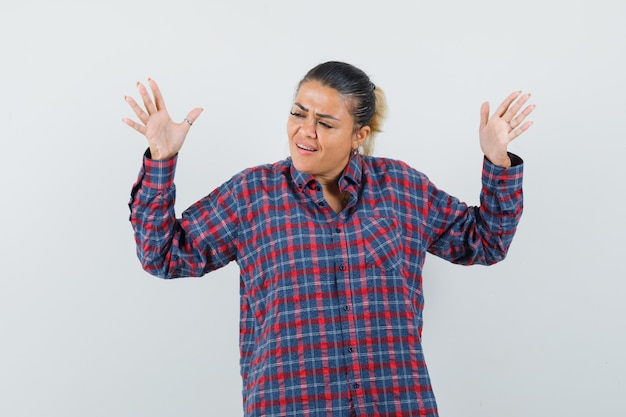 Senhora de camisa casual, levantando as mãos e parecendo irritada, vista frontal.