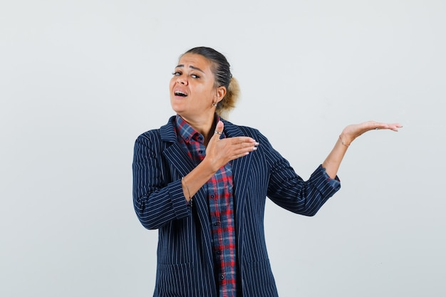 Senhora de camisa, jaqueta mostrando algo ou dando boas-vindas e parecendo confiante, vista frontal.