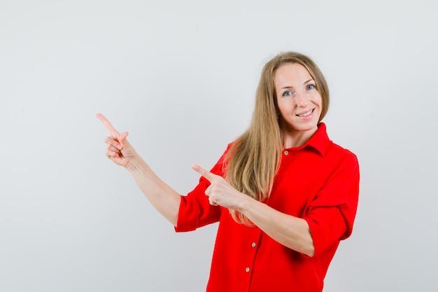 Senhora de camisa vermelha apontando para o canto superior esquerdo e parecendo feliz,