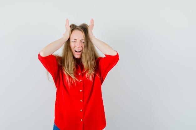 Senhora de camisa vermelha segurando as mãos na cabeça e parecendo melancólica,