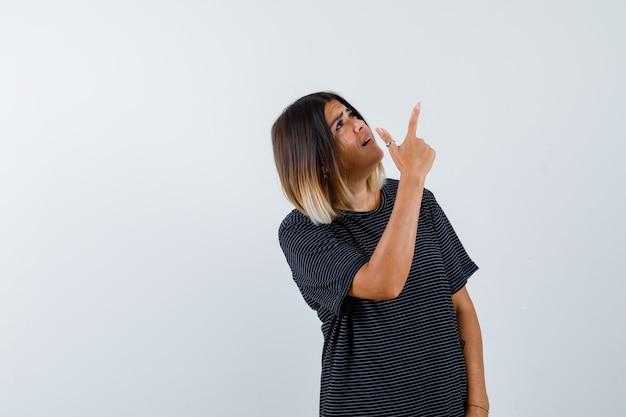 Senhora de camiseta preta apontando para cima e parecendo esperançosa, vista frontal.