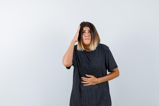 Senhora de camiseta preta, mantendo a mão na cabeça e parecendo ansiosa, vista frontal.