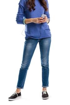 Senhora de camisola segura o telefone. calça jeans e sapatos simples. novo smartphone de marca famosa. a tecnologia é nossa melhor amiga.