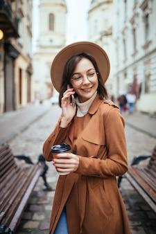 Senhora de casaco marrom, falando no celular, caminhando ao ar livre em dia frio de outono