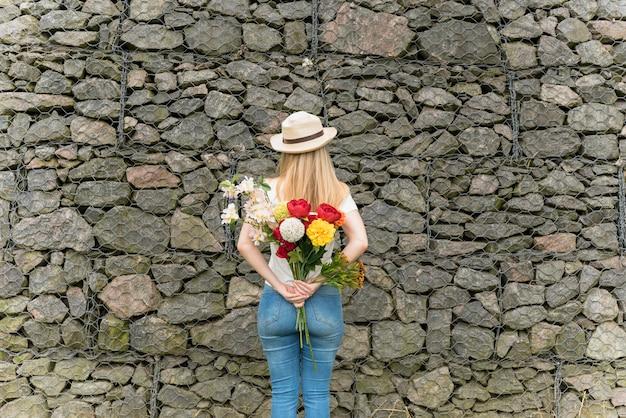 Senhora de chapéu com buquê de flores de volta perto da parede