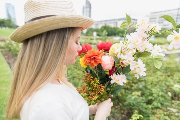 Senhora de chapéu com buquê de flores no parque da cidade