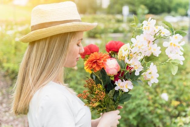 Senhora de chapéu com buquê de flores no parque
