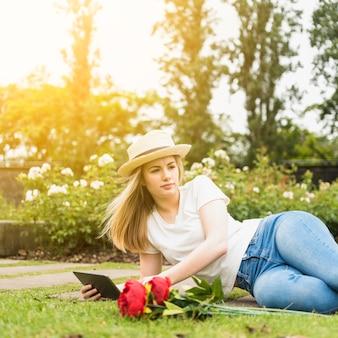 Senhora de chapéu usando tablet e deitada na grama perto de flores no parque