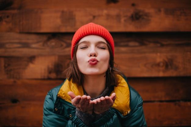 Senhora de chapéu vermelho mandando beijo no ar com os olhos fechados