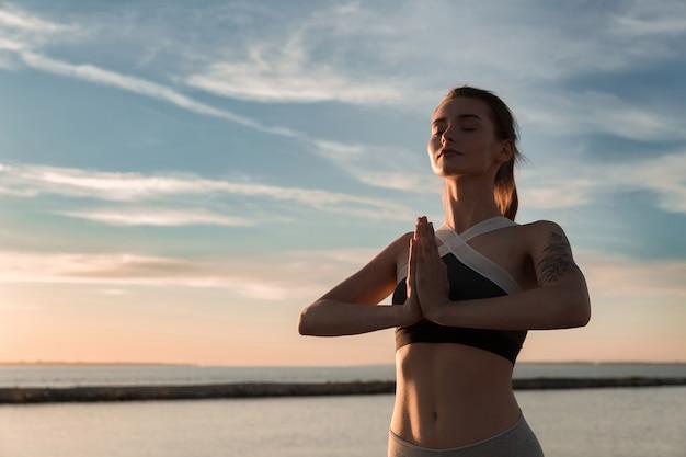Senhora de esportes na praia fazer meditar exercícios.