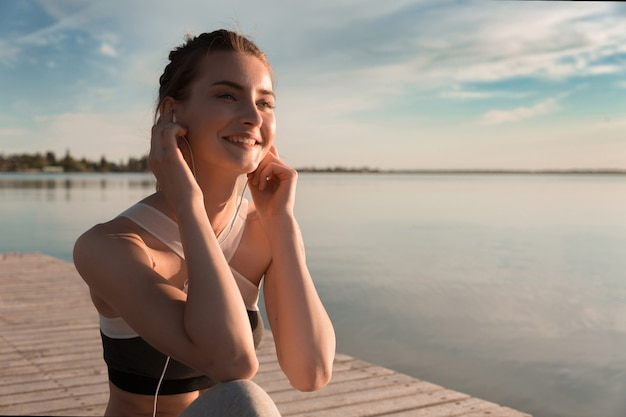 Senhora de esportes sorridente na praia ouvindo música com fones de ouvido