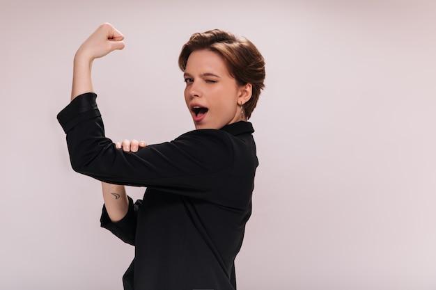 Senhora de jaqueta preta mostra bíceps em fundo isolado. mulher bonita em um terno escuro demonstra força e músculos