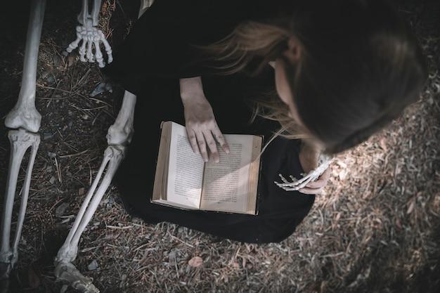 Senhora de leitura em roupas escuras perto de ossos