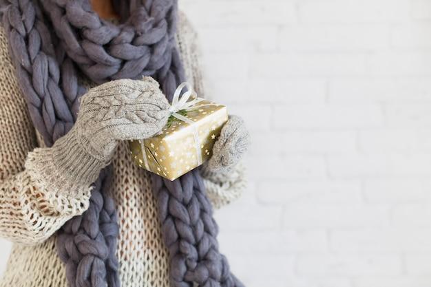 Senhora de luvas e cachecol com caixa de presente nas mãos