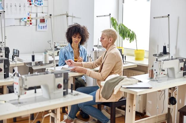 Senhora de meia-idade com assistente afro-americana juntos trabalhando em roupas no estúdio