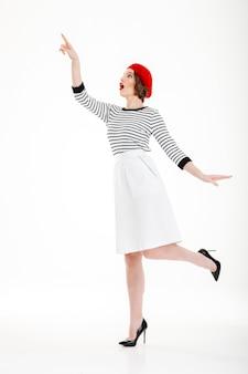 Senhora de moda jovem espantado apontando para cima no espaço da cópia isolado