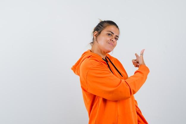 Senhora de moletom laranja apontando para o lado e parecendo confiante