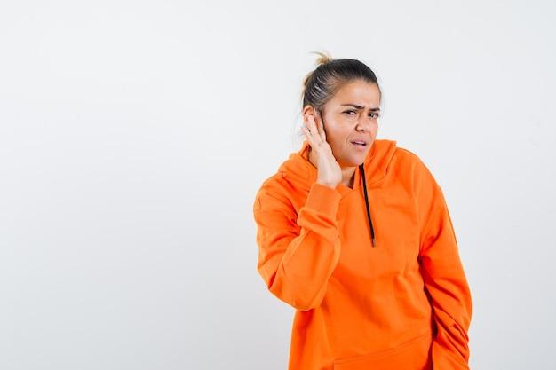 Senhora de moletom laranja ouvindo uma conversa particular e parecendo confusa
