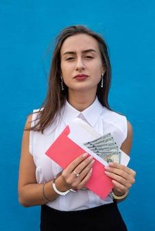 Senhora de negócios algemada, segurando um envelope com dólares. conceito de suborno e corrupção