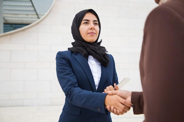Senhora de negócios confiante reunião e agradecendo colega fora
