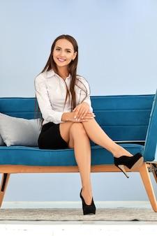 Senhora de negócios feliz sentado no sofá