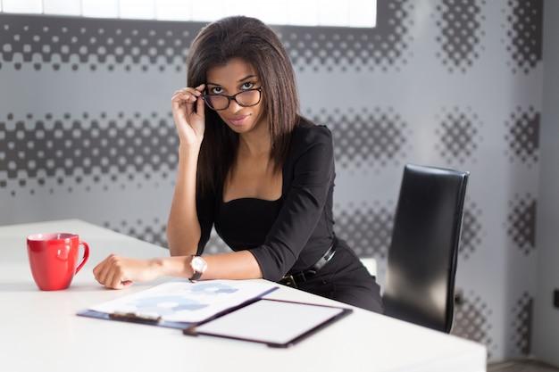 Senhora de negócios jovem bonito na suite forte preta sentar na mesa de escritório