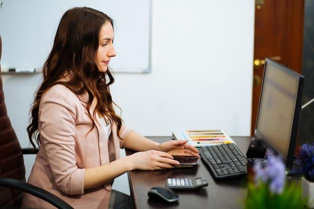 Senhora de negócios jovem de cabelos castanhos com cabelos longos, sentado na cadeira de escritório onn mesa, ansioso para um monitor de computador.