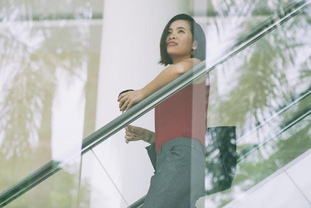 Senhora de negócios na escada rolante