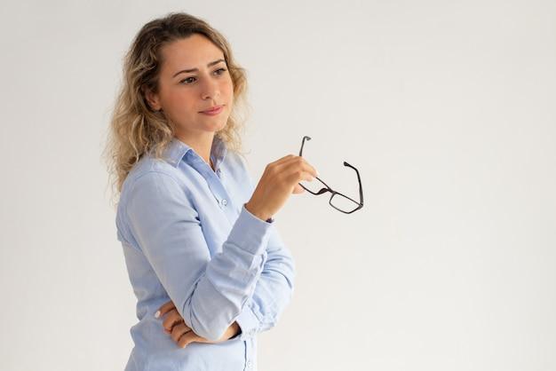 Senhora de negócios pensativo sonhador segurando óculos e desviar o olhar