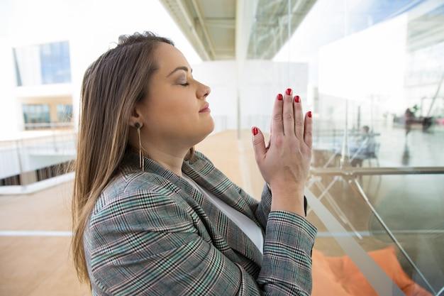 Senhora de negócios rezando e mantendo as mãos juntas ao ar livre