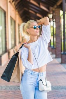 Senhora de óculos de sol segurando sacos no ombro
