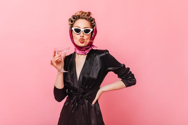 Senhora de óculos escuros posando na parede rosa, segurando uma taça de martini e comendo azeitona