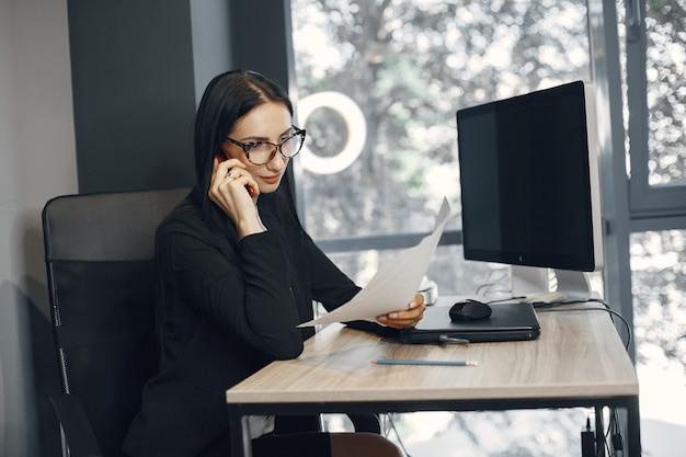 Senhora de óculos. o gerente está sentado em frente ao computador. a empresária trabalha em seu escritório.